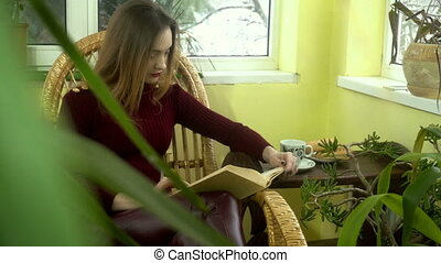 young beautiful girl reading a book in a wicker chair near the window with a lot of green plants around