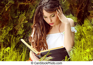 Young beautiful girl reading a book on green background of...