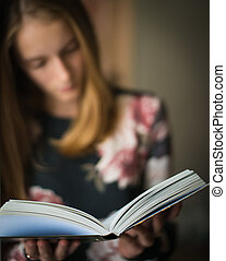 young beautiful girl reading a book