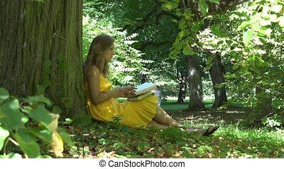 young beautiful girl reading book sitting near tree and people walking in the park. 4K