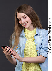 Young beautiful girl reads a text message on a cell phone