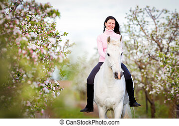 Young beautiful girl riding a horse