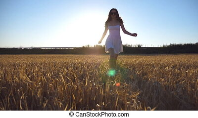 Young beautiful girl running along the wheat field with sun flare at background. Caucasian woman jogging to the camera at the beautiful meadow. Front view Slow motion Close up
