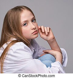 Young beautiful girl. Serious model with hand near face