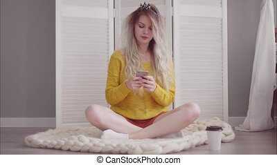 Young beautiful girl sits on the floor in her bedroom and using a smartphone. The wind blows the hair.