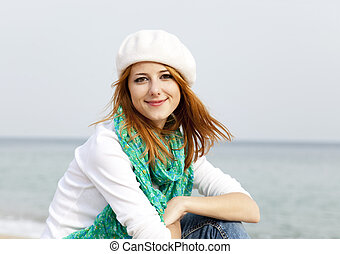 Young beautiful girl sitting at the beach.