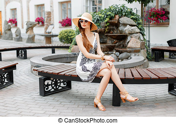 Young beautiful girl sitting on a bench in a sunny summer day.