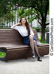 Young beautiful girl sitting on a bench in the summer park