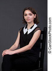 young beautiful girl sitting on a Chair