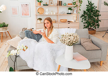 Young beautiful girl sitting on a couch with cup of coffee