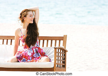 young beautiful girl sitting on beach sofa on sea background