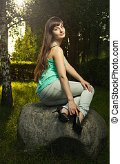 young beautiful girl sitting on the big stone in park