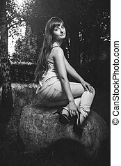 girl sitting on the big stone in park