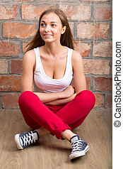 Young beautiful girl sitting on the floor