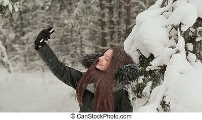 Young beautiful girl smiles into camera phone in snow-covered winter forest. Enjoying the winter beauty and falling snow.