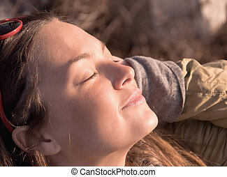 Young beautiful girl smiling. Squinting in the glow of the ...