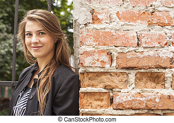 Young beautiful girl standing on a street near the brick wall. Close-up.