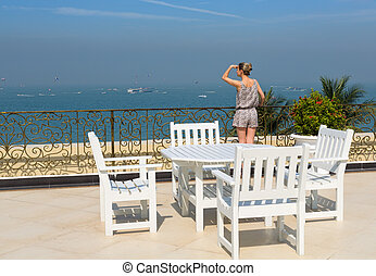 Young beautiful girl standing on the balcony of the restaurant of the hotel and looks into the distance. One Caucasian woman is back side