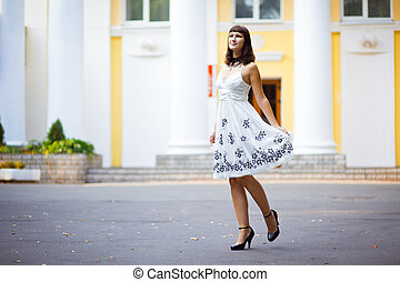 Young beautiful girl stands in front of house