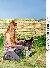 young beautiful girl stroking a small goat