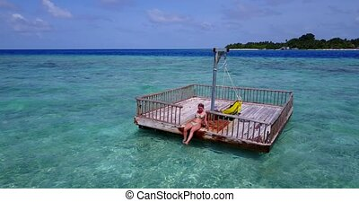 young beautiful girl sunbathing on pontoon with drone aerial...