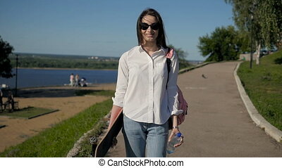 Young Beautiful Girl Walking at Park Holding a Skateboard