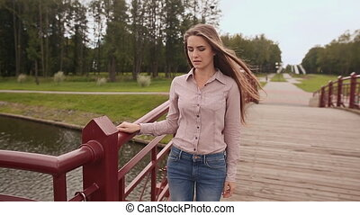 Young beautiful girl walking on the bridge across the lake in the Park. She sings the song.