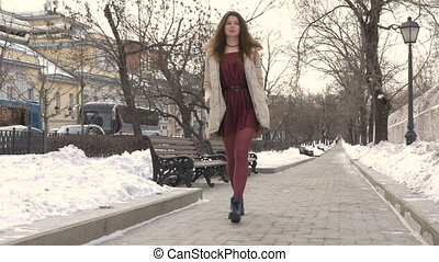 Young beautiful girl walking through the city streets.