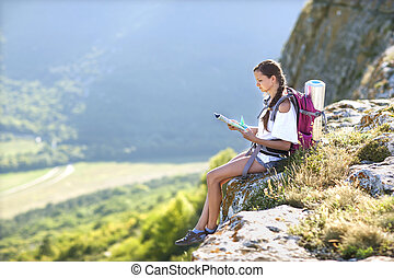 Young, beautiful girl with a backpack on her back, studying a ma