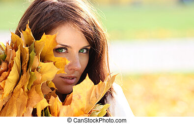 young beautiful girl with a bouquet of maple leaves