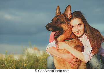 Young beautiful girl with a German shepherd playing on the lawn