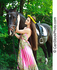 Young beautiful girl with a horse in green forest