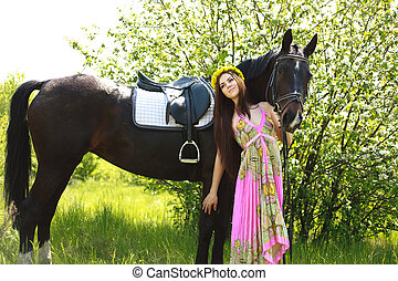 Young beautiful girl with a horse in summer garden