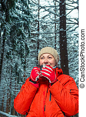 young beautiful girl with a metal mug of hot tea in the winter forest