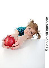 Young beautiful girl with a red apple on the table.