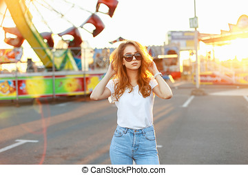 Young beautiful girl with bright red hair standing in the amusement park on a summer day at sunset.