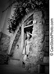 young beautiful girl with hat posing near a vintage door