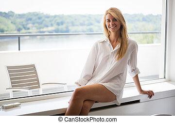 Young beautiful girl with long brown hair in white men shirt