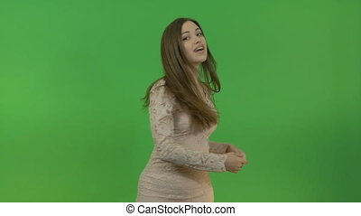Young beautiful girl with long hair asks a question and points to three objects behind her back. On the green screen.