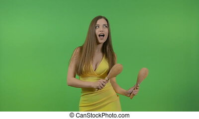 Young beautiful girl with long hair dancing with maracas. Fun and cheerful, on a green background.