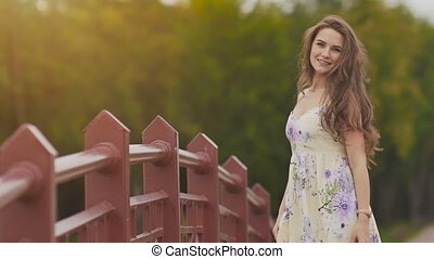 Young beautiful girl with long hair in a light dress posing on the camera leaning on a railing bridge in the park. Summer. Youth. Beauty.