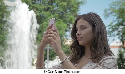 Young beautiful girl with long hair takes a picture of herself on the phone. In the city park, near the fountain