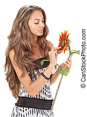 Young beautiful girl with long hairs holding sunflower on white