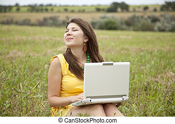 young beautiful girl with notebook at field