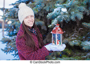 Young beautiful girl with red Christmas lantern in the snow