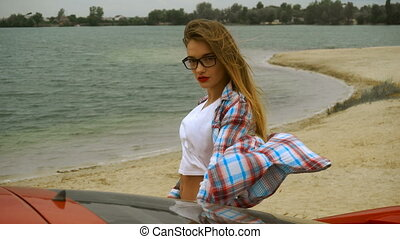 young beautiful girl with red lips and glasses stand on a seashore
