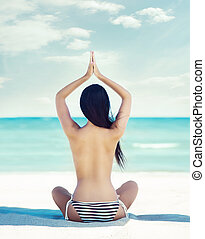 Young, beautiful girl with sexy body meditating on a beach...