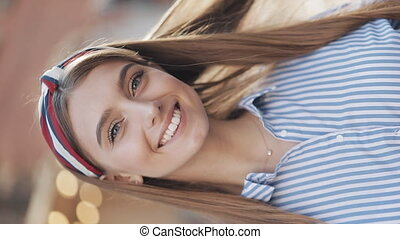 Young Beautiful Girl with Stylish Headband Wearing in Striped Dress Turning Head to Camera Swapping Hair and Smiling Looking to Camera Standing at the City Street Vertical Video. Close Up