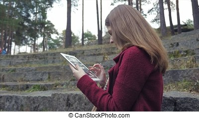 Young beautiful girl with tablet sitting on stairs in park...