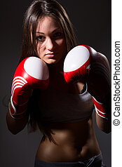 Young beautiful girl with the boxing gloves